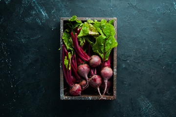 Fotomurales - Fresh beetroot with leaves on a black stone background. Healthy food. Top view. Free space for your text.