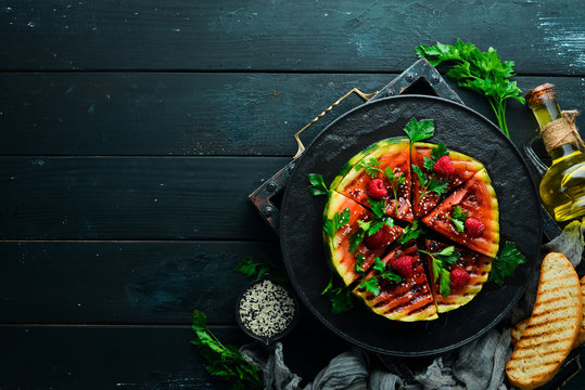 Grilled watermelon with raspberries and parsley on a black plate. Top view. Free copy space.