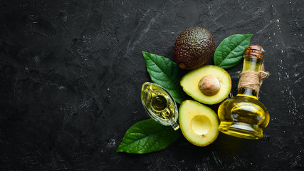 Avocado oil and fresh avocados on a black background. Rustic style. Top view. Free space for your text.