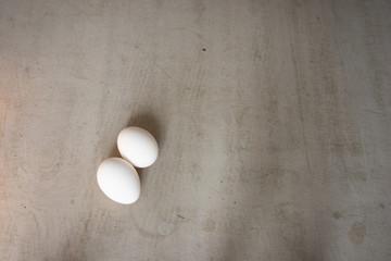 Fotobehang Two eggs lying on a gray concrete table