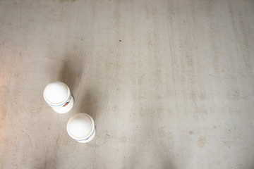 Fotobehang two eggs in cups standing on concrete table
