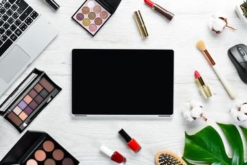 Female cosmetics on white office desk. Laptop, notepad, Lipstick, powder, comb, women's jewelry. Top view. Free space for your text. Flat lay.