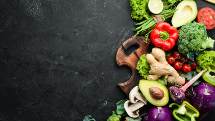 Fresh vegetables on a black background. Vegetarian food. Top view. Free space for your text.