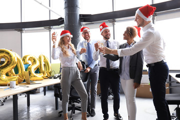 Business people are celebrating holiday in modern office drinking champagne and having fun in coworking. Merry Christmas and Happy New Year 2020 Wall mural