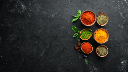 Fototapete - Colorful herbs and spices for cooking. Indian spices. On a black stone background. Top view.