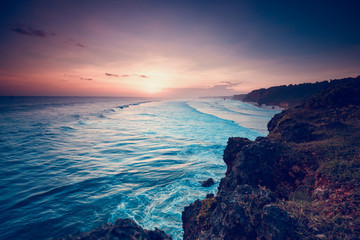 Sumba Island Indonesia Beautiful Sunset Coastline. Rural Asian Country Nature Seaside. Scenic Tourism Beach Coast Place. Amazing View from Stone Hill on Ocean Waves, Sun and Sky. Panoramic Photography