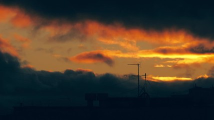 Fotobehang - Epic sunset clouds moving over old antenna on city skyline rooftop. Timelapse, 4K UHD.