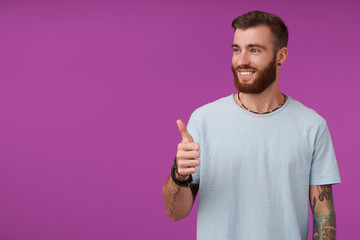 Cheerful young handsome unshaved male with tattooes looking aside with sincere wide smile and showing raised thumb, wearing blue t-shirt while posing over purple background