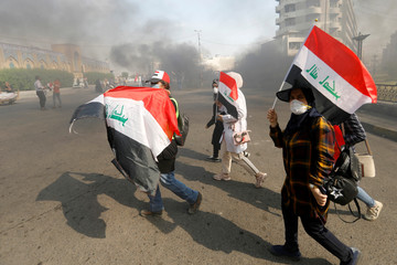 Iraqi demonstrators carry Iraqi flags as they walk at a cloud of smoke during ongoing anti-government protests, in Baghdad
