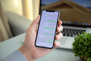 Man holding iPhone X with social networking service WhatsApp