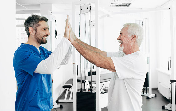 Senior man and Physical Therapist have five after successful physio treatment. physio rehabilitation