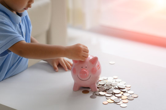 hand of a little boy try to saving money for future, learning to save budget for future