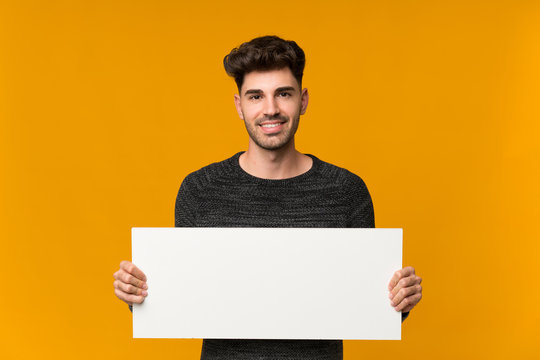Young man over isolated background holding an empty white placard for insert a concept
