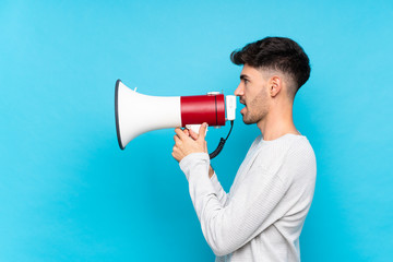 Young man over isolated blue background shouting through a megaphone