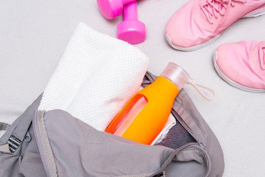 Woman folds things in a sports bag, water bottle