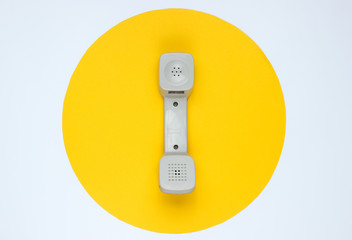 Retro telephone handset on white background with yellow circle. Pop culture. 80s. Minimalistic fashion shot. Top view