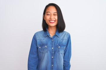 Young beautiful chinese woman wearing denim shirt standing over isolated white background winking looking at the camera with sexy expression, cheerful and happy face.