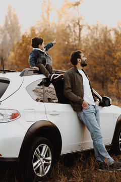 Happy father stanting near the car with his son sitting on car and pointing at sky.