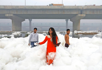 People pose for pictures as they stand amidst the foam covering the polluted Yamuna river on a smoggy morning in New Delhi