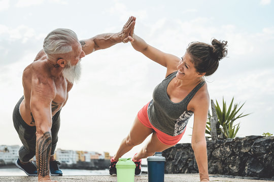 Fitness couple doing push ups exercise outdoor - Happy athletes making workout session outside - Concept of people training and bodybuilding lifestyle