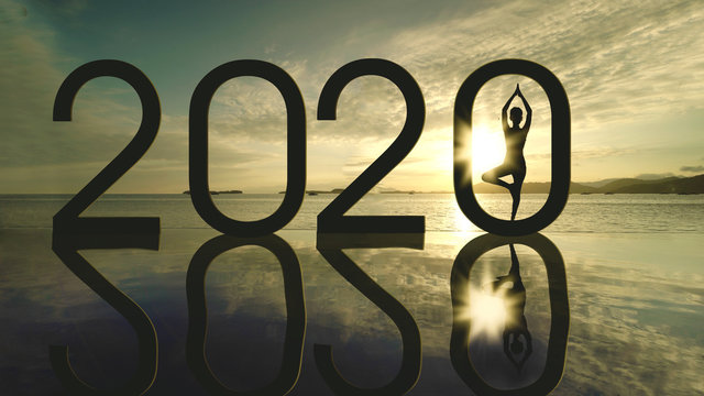 Woman doing yoga with number 2020 on beach