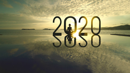 Woman practices yoga with number 2020 on beach