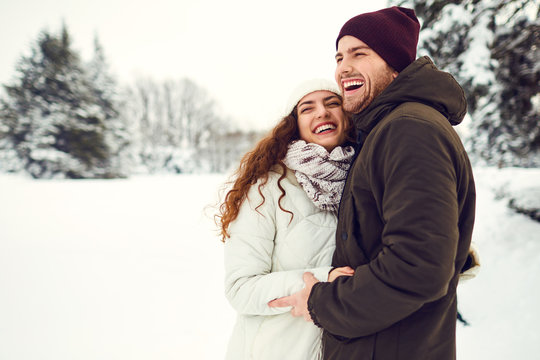 Young couple on the snow in winter in the park