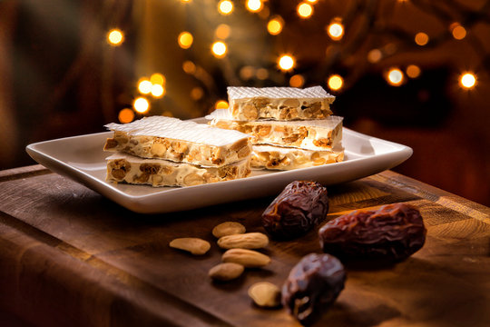 Christmas Concept. Alicante nougat in the foreground, in a warm home atmosphere at Christmas. There are Christmas lights in the background.