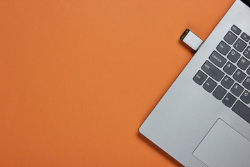 Laptop with flash drive on brown paper background. Studio shot, top view. Wall mural