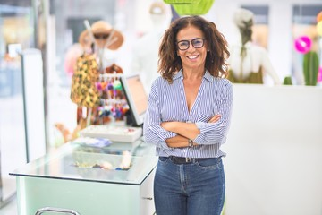 Middle age beautiful clothes shop owner woman smiling happy and confident waiting customers at...