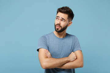Young pensive handsome man in casual clothes posing isolated on blue background, studio portrait. People sincere emotions lifestyle concept. Mock up copy space. Holding hands crossed, looking aside.