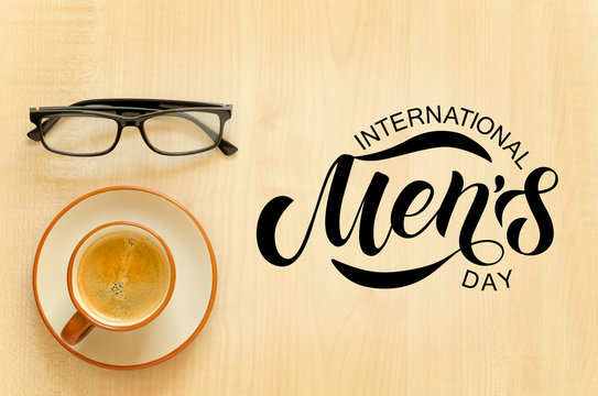 Desktop with notebook, pencil, eyeglasses and coffee cup. Hand sketched International Men's day text.