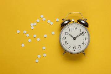 Time to take pills. Pills and alarm clock on yellow background. Top view