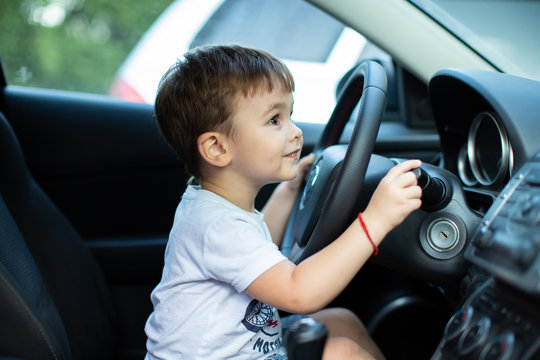 Little boy sitting behind the wheel of a car with a lovely smile on his face, outdoors, family travel concept