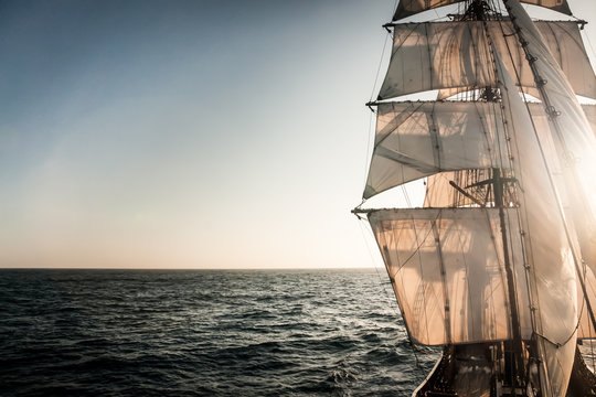 Backlit sails of a traditional tall ship on the atlantic