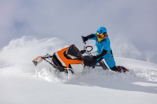 the guy turns a snowmobile in a mountain valley on the background of the clear snow and sky, leaving behind a trail of splashes. bright snow bike and suit without brands. Boondocker sports snowmobile