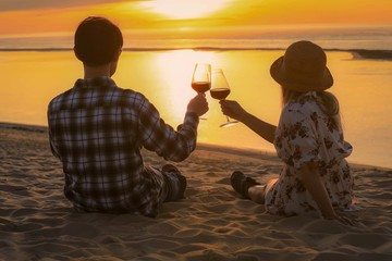 Couple celebration drinking red wine at sunset on the beach