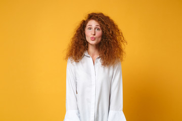 Pretty funny young redhead woman girl in casual white shirt posing isolated on yellow orange background, studio portrait. People sincere emotions lifestyle concept. Mock up copy space. Blowing lips.