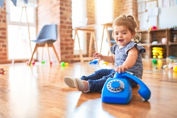 Beautiful toddler sitting on the floor playing with vintage phone at kindergarten