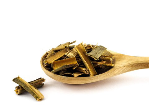 Dry willow bark lies in a wooden spoon on a white background