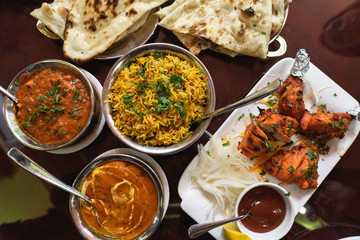 Assortment of Indian dishes for dinner, butter chicken, tikka masala, rice and naan