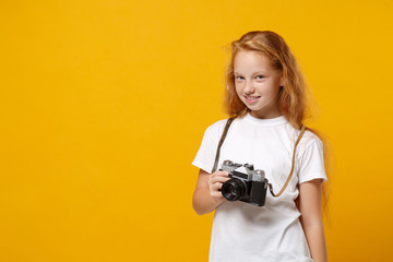Smiling little ginger kid girl 12-13 years old in white t-shirt isolated on yellow wall background children portrait. Childhood lifestyle concept. Mock up copy space. Hold retro vintage photo camera.