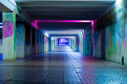 Long luminous tunnel with colorful walls. Underpass with neon lamps