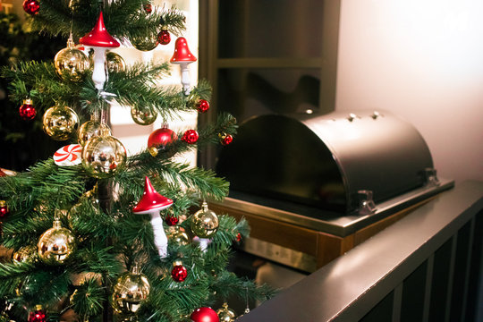 Christmas atmosphere, interior. Christmas tree decorated with toys. Grilling food at home. Barbecue, bbq.