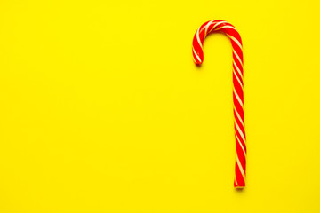 Christmas candy cane on yellow background