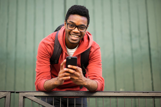 smiling young african american man with glasses and mobile phone