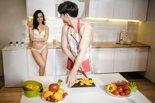 Young sexy couple after intimacy in kitchen in night. Careful well-built shirtless man cut fruit and look bac at woman. She stand behind and hold glass of juice. Wearing sexy white lingerie.