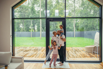 Lovelt parents kissing. Beautiful and happy family together at home with panoramic window standing. Hug each other Wall mural