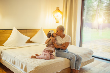 Happy family enjoy at home. Mother and daughter sitting on bed, hug each other and kiss. Isolated in light bedroom with panoramic window. Family, relatives, home concept Wall mural