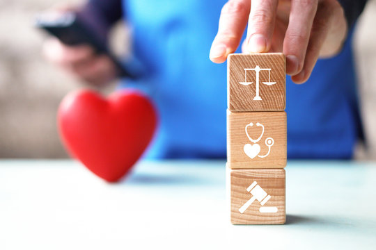 Doctor hand arranging wood block stacking with icon  justice healthcare Labor Law Lawyer Legal Concept medical.